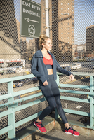 Female athlete standing by fence in city during sunny day