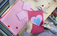 Midsection of girl making Valentine card at home