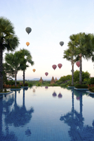 Hot air balloons and palm trees reflecting in swimming pool at Bagan