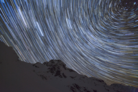 Low angle view of star trail against silhouette mountain at night