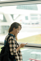 Woman using mobile phone while standing by window in airport departure area 11100058893| 写真素材・ストックフォト・画像・イラスト素材|アマナイメージズ