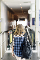 Rear view of woman walking towards moving walkway in airport 11100058896| 写真素材・ストックフォト・画像・イラスト素材|アマナイメージズ