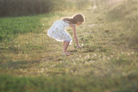 Side view of girl picking flower while standing on grassy field