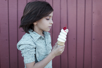 Boy holding ice cream while standing by wall 11100058973| 写真素材・ストックフォト・画像・イラスト素材|アマナイメージズ