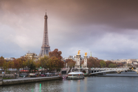 Eiffel Tower by Seine river against cloudy sky