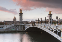 Pont Alexandre III over Seine River against cloudy sky during sunset