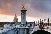 Les Invalides Quarter by Pont Alexandre III against cloudy sky during sunset