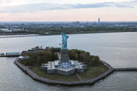 Statue of Liberty by island against sky in city
