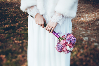 Midsection of bride holding bouquet while standing on field 11100059067| 写真素材・ストックフォト・画像・イラスト素材|アマナイメージズ
