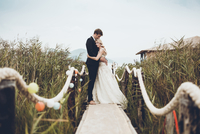 Couple embracing while standing on footbridge amidst plants
