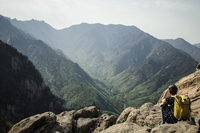Rear view of hiker sitting on rocks against mountains 11100059103| 写真素材・ストックフォト・画像・イラスト素材|アマナイメージズ