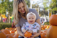 Portrait of happy baby girl holding pumpkin while sitting with mother at yard during Halloween