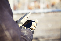 Cropped hands of worker using mobile phone at construction site