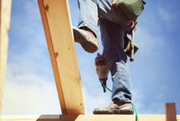 Low section of worker with drill standing on wooden frame against sky 11100059255| 写真素材・ストックフォト・画像・イラスト素材|アマナイメージズ