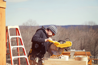 Worker cutting wooden planks with circular saw during sunny day