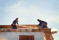 Workers constructing roof beam against sky during sunny day 11100059268| 写真素材・ストックフォト・画像・イラスト素材|アマナイメージズ
