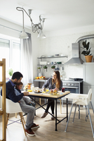 Parents with son having breakfast at table in kitchen 11100059322| 写真素材・ストックフォト・画像・イラスト素材|アマナイメージズ