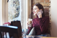 Woman with drink looking through window while talking on mobile phone in cafe 11100059345| 写真素材・ストックフォト・画像・イラスト素材|アマナイメージズ