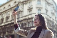 Woman taking selfie while standing on city street 11100059354  写真素材・ストックフォト・画像・イラスト素材 アマナイメージズ