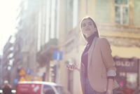 Woman holding mobile phone looking away while standing on city street 11100059356  写真素材・ストックフォト・画像・イラスト素材 アマナイメージズ