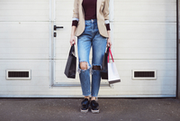 Low section of woman holding shopping bags while standing by closed door 11100059357| 写真素材・ストックフォト・画像・イラスト素材|アマナイメージズ