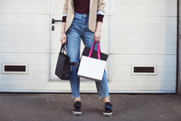 Low section of woman with shopping bags while standing by closed door 11100059358| 写真素材・ストックフォト・画像・イラスト素材|アマナイメージズ