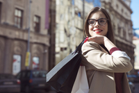 Happy woman with shopping bags looking away while standing on city street 11100059362  写真素材・ストックフォト・画像・イラスト素材 アマナイメージズ