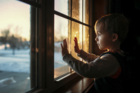 Boy looking through window while standing in darkroom at home 11100059381  写真素材・ストックフォト・画像・イラスト素材 アマナイメージズ