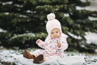 Baby girl sitting on blanket during snowfall