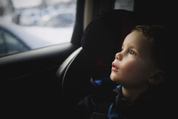Thoughtful boy looking up while traveling in car 11100059424| 写真素材・ストックフォト・画像・イラスト素材|アマナイメージズ