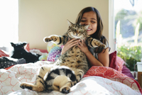 Happy girl with cat sitting on bed at home 11100059468| 写真素材・ストックフォト・画像・イラスト素材|アマナイメージズ