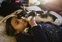Girl with cat relaxing on bed at home 11100059477| 写真素材・ストックフォト・画像・イラスト素材|アマナイメージズ
