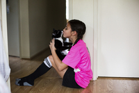 Girl kissing cat while sitting on floor at home