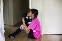 Girl kissing cat while sitting on floor at home 11100059515| 写真素材・ストックフォト・画像・イラスト素材|アマナイメージズ