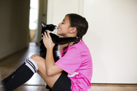 Playful girl kissing cat while sitting on floor at home