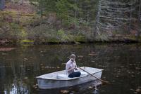 Man fishing while sitting in boat on lake