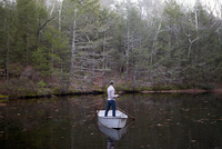 Side view of man fishing while standing in boat on lake