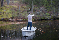 Rear view of man fishing while standing in boat on lake at forest