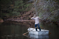 Man fishing in lake while standing on boat at forest