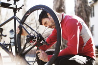 Male cyclist examining bicycle outdoors
