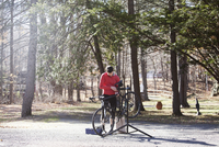 Athlete adjusting bicycle on road during sunny day