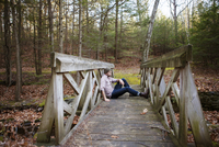 Side view of thoughtful man sitting on footbridge in forest 11100059633| 写真素材・ストックフォト・画像・イラスト素材|アマナイメージズ