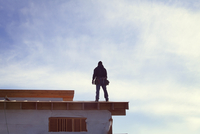 Low angle view of worker standing on roof beam during sunny day 11100059637| 写真素材・ストックフォト・画像・イラスト素材|アマナイメージズ