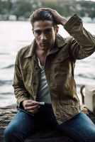 Portrait of man holding cigarette while sitting by river on log 11100059672| 写真素材・ストックフォト・画像・イラスト素材|アマナイメージズ