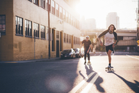Friends skateboarding on city street against sky during sunny day