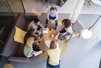 High angle view of business people discussing in meeting at office 11100059708| 写真素材・ストックフォト・画像・イラスト素材|アマナイメージズ