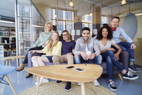 Portrait of happy business people sitting on sofa in office 11100059714| 写真素材・ストックフォト・画像・イラスト素材|アマナイメージズ