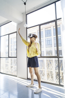 Businesswoman using virtual reality simulator while standing by window in office 11100059733| 写真素材・ストックフォト・画像・イラスト素材|アマナイメージズ