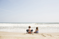 Rear view of siblings enjoying at beach against sky during sunny day 11100059918| 写真素材・ストックフォト・画像・イラスト素材|アマナイメージズ