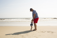 Father and daughter enjoying at beach against sky during sunny day